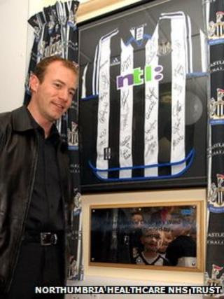 Alan Shearer with the shirt presented to North Tyneside General Hospital