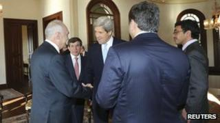 US Secretary of State John Kerry (3rd left), accompanied by Turkish Foreign Minister Ahmet Davutoglu (2nd left) chats with Egypt's Foreign Minister Mohamed Kamel Amr (left)