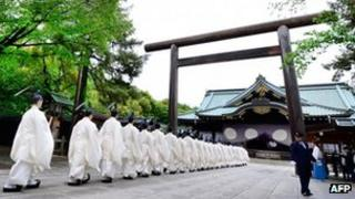 Shinto priests walk in line to the main shrine during the three-day annual spring festival at the Yasukuni Shrine in Tokyo on 21 April 2013