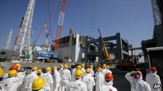 Journalists inspect damaged No.4 reactor building at Fukushima Daiichi nuclear power plant