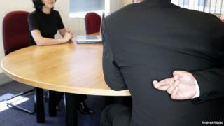 Generic image of a man in a meeting with his fingers crossed behind his back