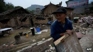 An elderly man holds a sign asking for help outside his destroyed home in Longmen village after a magnitude 7.0 earthquake hit Lushan, Sichuan Province on April 22, 2013