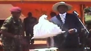 President Yoweri Museveni holding a bag of money