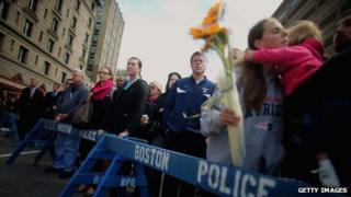 People gather during a moment of silence honouring the Boston Marathon bombing victims in Copley Square, near the bombing sites in Boston, Massachusetts, 22 April 2013