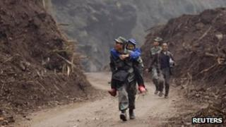 A soldier carrying a 60-year-old survivor in Lingguan township, which was recently cleared of debris from landslides caused by Saturday's earthquake, in Baoxing county in Ya'an, Sichuan province, 22 April 2013