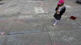 A girl walks amid chalk messages written by passerbys about the Boston Marathon bombing