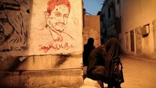 A tear-gassed woman sits next to a mural of jailed activist Abdulhadi al-Khawaja