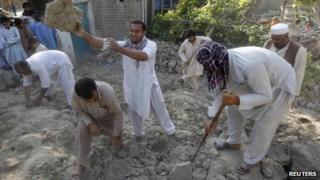 Earthquake survivors work on the rubble of a mud house after it collapsed following the quake in Jalalabad province, 24 April 2013
