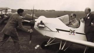 Prince Philip sits in the plane while Sir John Severne spins the propeller.