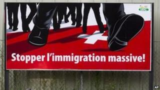 "A poster of the right-wing Swiss People's Party (SVP) which shows feet walking on the Swiss cross and the message ""Stop mass immigration"" (2 Aug 2011)"