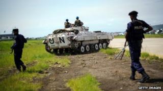 Congolese government policemen walk alongside a United Nations armoured personnel carrier at the airport in Goma, eastern Democratic Republic of the Congo