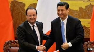 French President Francois Hollande and Chinese President Xi Jinping shake hands
