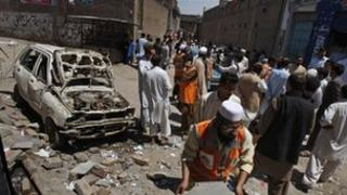 People gather at the site of an explosion outside an election office of a candidate in Peshawar, Pakistan, 28 April 2013