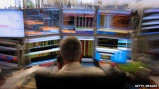Stock market trader on the phone in front of screens