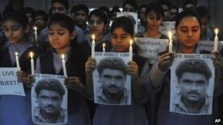 Indian school children hold photographs of Sarabjit Singh, an Indian spy on death row in Pakistan as they light candles and pray for his recovery in Amritsar, India, on 29 April 2013