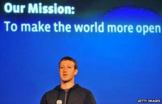 """Facebook CEO Mark Zuckerberg against a backdrop reading: """"Our Mission: To make the world more open"""""""