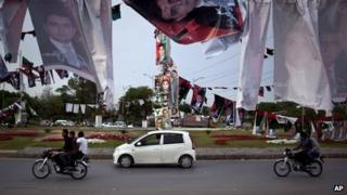 Pakistani motorists ride past banners and posters of various candidates for upcoming elections, hanged with poles at a roundabout in Islamabad, Pakistan on Saturday, April 27, 2013.