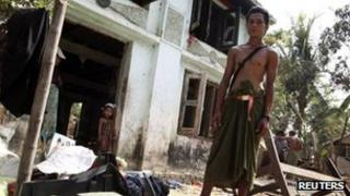 Ko Ko Naing, a Muslim man, stands in front of his home, damaged by Buddhist mobs the previous day, in Kyaw Boi Lay village on 1 May 2013