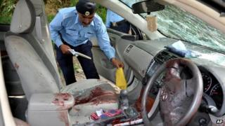 A police officer examines the car of prosecutor Chaudhry Zulfikar Ali