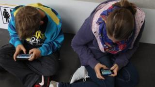 children playing on their phones