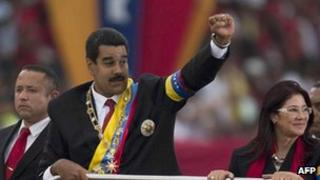 Venezuelan President Nicolas Maduro (centre) raises his clenched fist after taking office in April