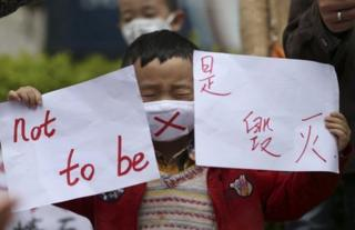 A child holds up protest posters in Kunming, China, 4 May