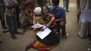 A woman is comforted after identifying the body of her daughter, a victim of the garment factory collapse in Savar, near Dhaka, Bangladesh, 5 May 2013