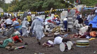Wounded churchgoers lie on the ground as Catholic nuns run for cover after the blast in Arusha (5 May 2013)