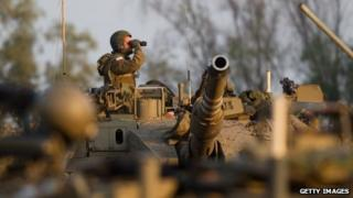 Israeli soldier looks through his binoculars