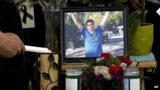 A mourner light candles at a makeshift memorial for Ricardo Portillo in Salt Lake City, Utah, on 5 May 2013