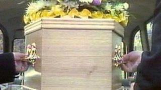 Coffin being placed into a hearse