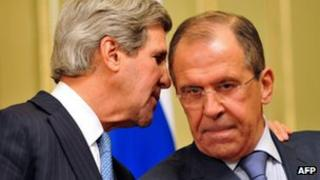 US Secretary of State John Kerry whispers to Russian Foreign Secretary Sergei Lavrov