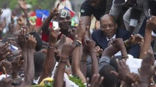 Former Haitian President Jean-Bertrand Aristide, right, greets supporters outside the courthouse in Port-au-Prince, Haiti, on Wednesday