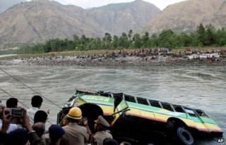 Rescuers look at a bus that plunged into the Beas River near Kullu, India, Wednesday, May 8, 2013