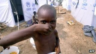Child eating at a refuge camp in DR Congo