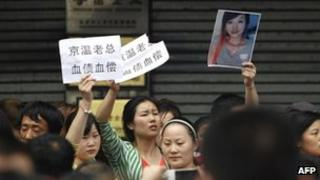 This picture taken on 8 May 2013 shows protesters holding banners and a photo of a young woman who fell to her death at a wholesale clothing centre in Beijing