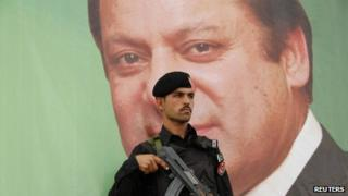 A paramilitary soldier guards in front of the portrait of Nawaz Sharif
