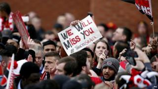 Fan holds placard in crowd at Old Trafford