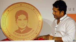 Sachin Tendulkar looks at a replica of a gold coin embossed with his face in Mumbai on May 13, 2013