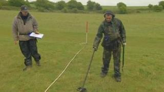 Metal detector searches on battlefield site