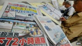 Newspapers show headlines carrying the story of a Taiwanese fisherman shot by Filipino coastguards, at a library in New Taipei City on 12 May 2013