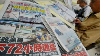 Newspapers show headlines carrying the story of a Taiwanese fisherman shot by Filipino coastguards, at a library in New Taipei City on May 12, 2013.