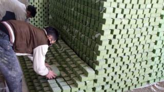 Workers stacking soap