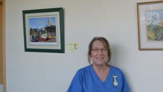 Jean Gomes beside two paintings