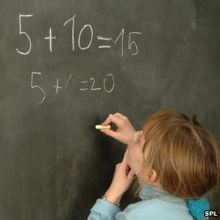 A child thinking about a sum at the blackboard