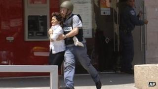 A woman being taken out of a bank in Beersheba, Israel, after a shooting, 20 May 2013