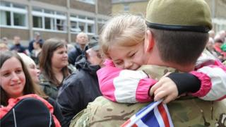 A girl hugs a soldier from the Duke of Lancaster's Regiment