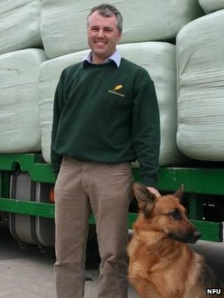 Andrew Hall and his dog standing in front of one of the lorries loaded with food