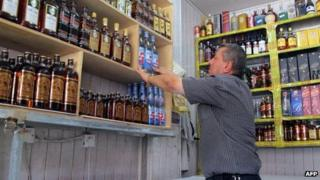 A shopkeeper arranges bottles in an alcohol shop in the Zayouna area of the Iraqi capital Baghdad, on 15 May 2013, the day after an attack on alcohol shops by gunmen