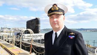 Commander Irvine Lindsay beside HMS Trenchant